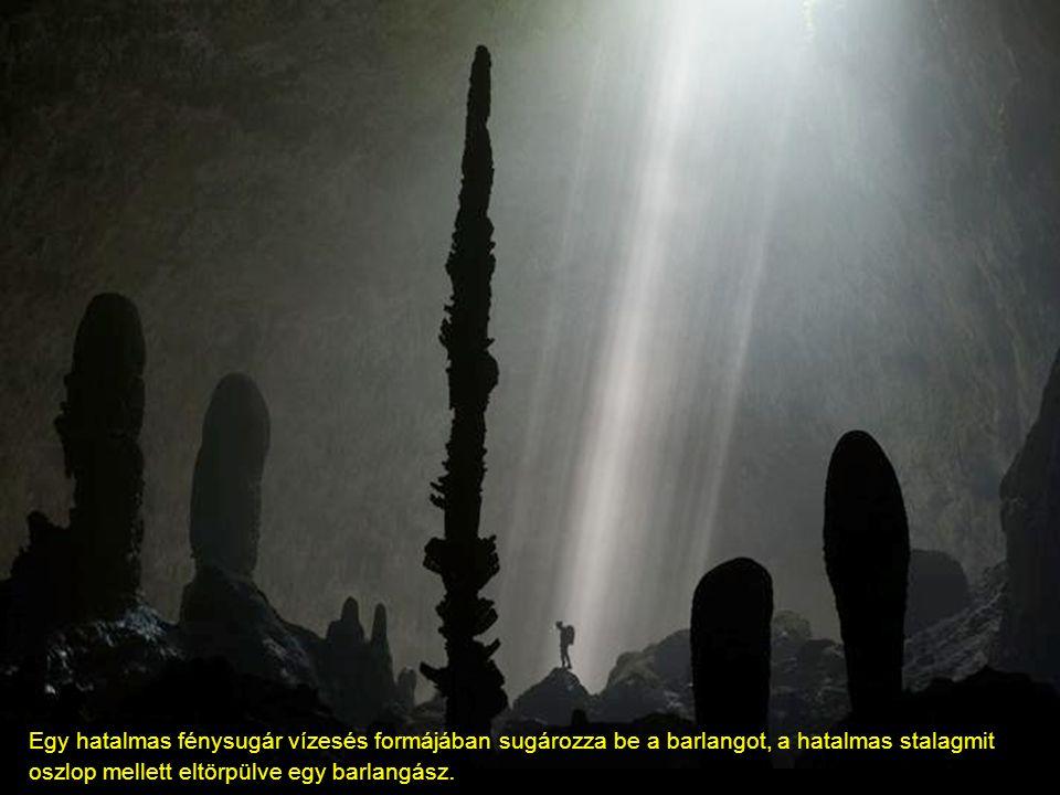 Egy hatalmas fénysugár vízesés formájában sugározza be a barlangot, a hatalmas stalagmit oszlop mellett eltörpülve egy barlangász.