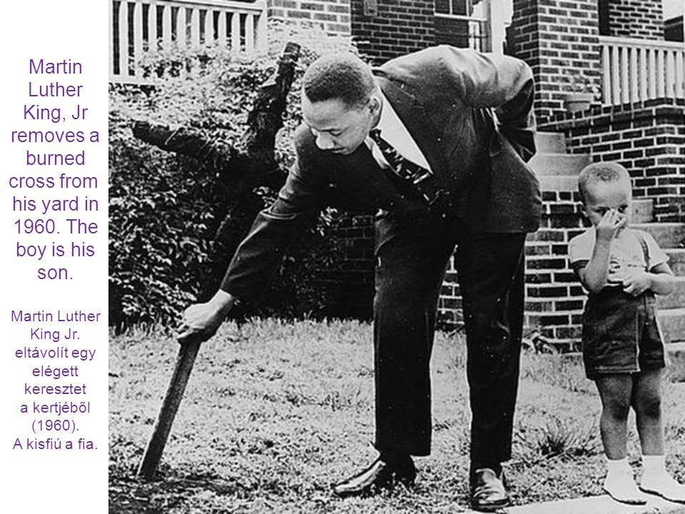 Martin Luther King, Jr removes a burned cross from