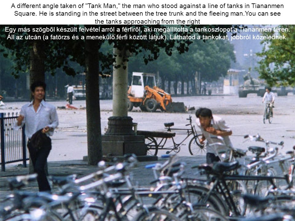 A different angle taken of Tank Man, the man who stood against a line of tanks in Tiananmen Square. He is standing in the street between the tree trunk and the fleeing man.You can see the tanks approaching from the right