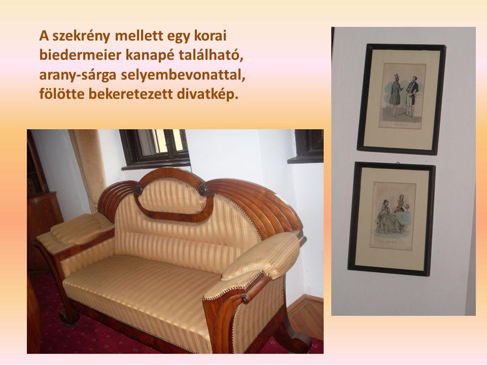 A szekrény mellett egy korai biedermeier kanapé található, arany-sárga selyembevonattal, fölötte bekeretezett divatkép.