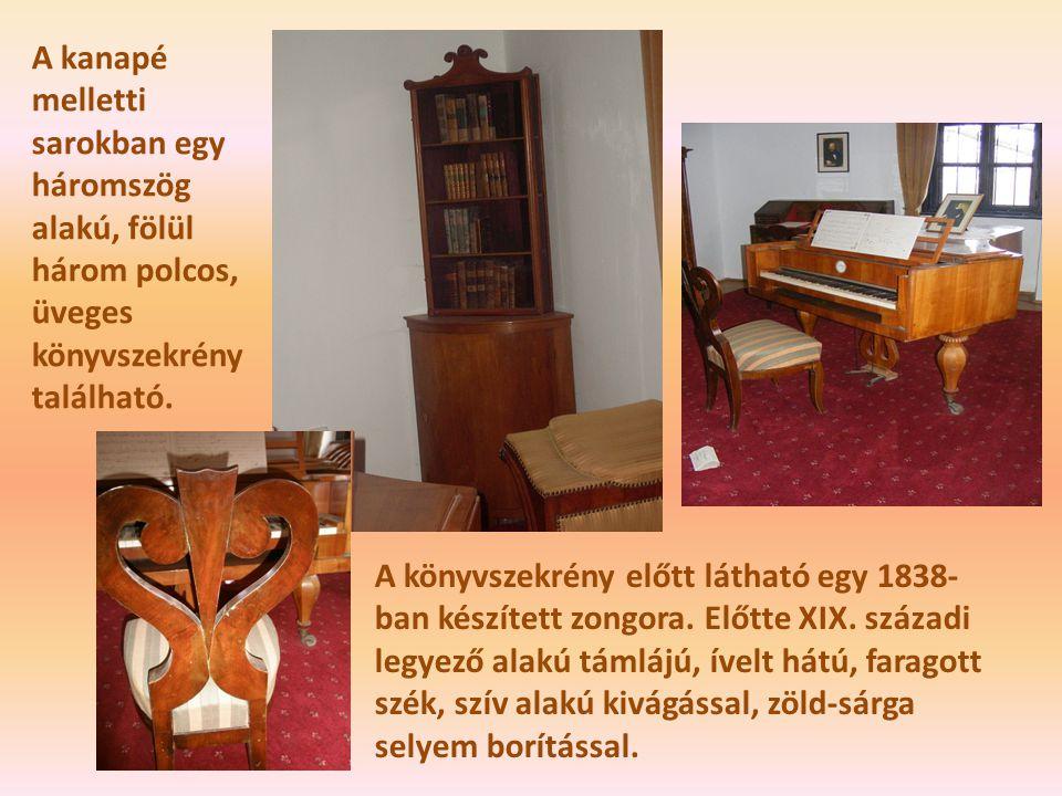 A kanapé melletti sarokban egy háromszög alakú, fölül három polcos, üveges könyvszekrény található.