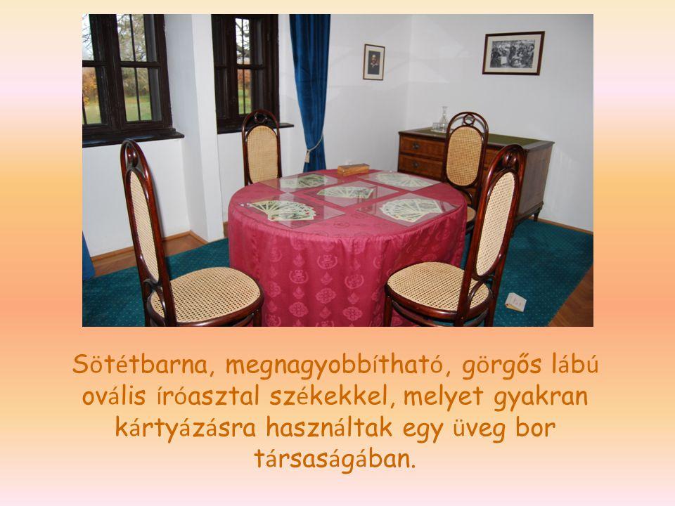 Sötétbarna, megnagyobbítható, görgős lábú ovális íróasztal székekkel, melyet gyakran kártyázásra használtak egy üveg bor társaságában.