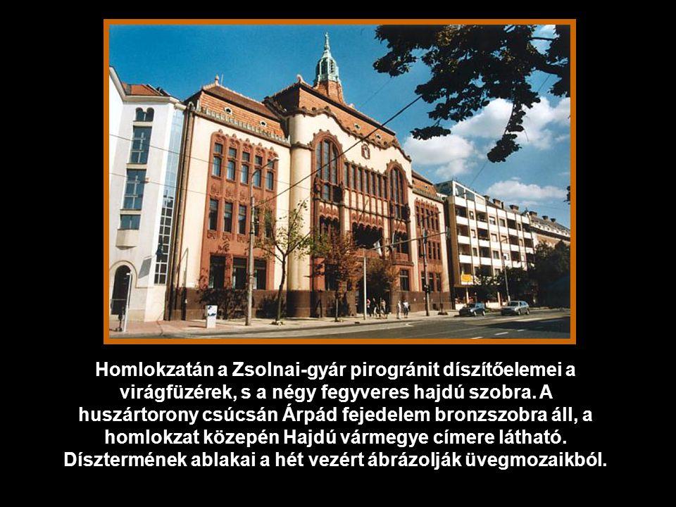 Homlokzatán a Zsolnai-gyár pirogránit díszítőelemei a virágfüzérek, s a négy fegyveres hajdú szobra.