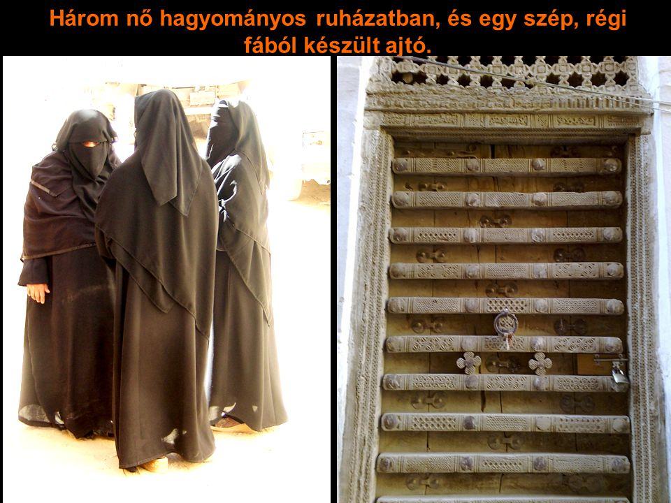 Három nő hagyományos ruházatban, és egy szép, régi fából készült ajtó.