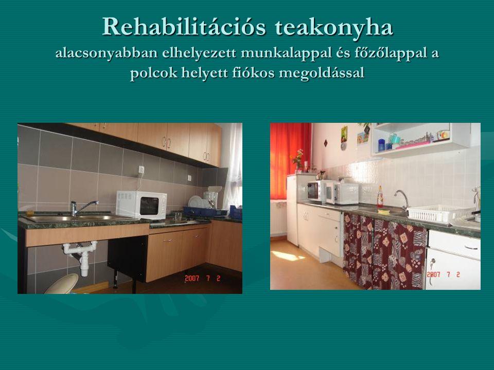 Rehabilitációs teakonyha alacsonyabban elhelyezett munkalappal és főzőlappal a polcok helyett fiókos megoldással