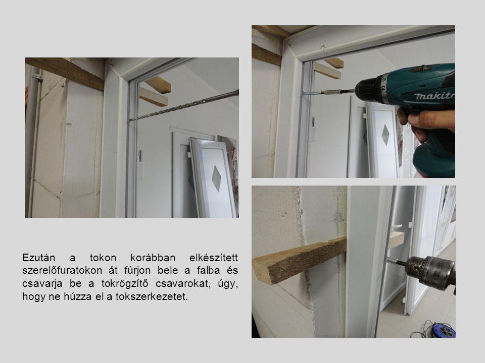 Ezután a tokon korábban elkészített szerelőfuratokon át fúrjon bele a falba és csavarja be a tokrögzítő csavarokat, úgy, hogy ne húzza el a tokszerkezetet.