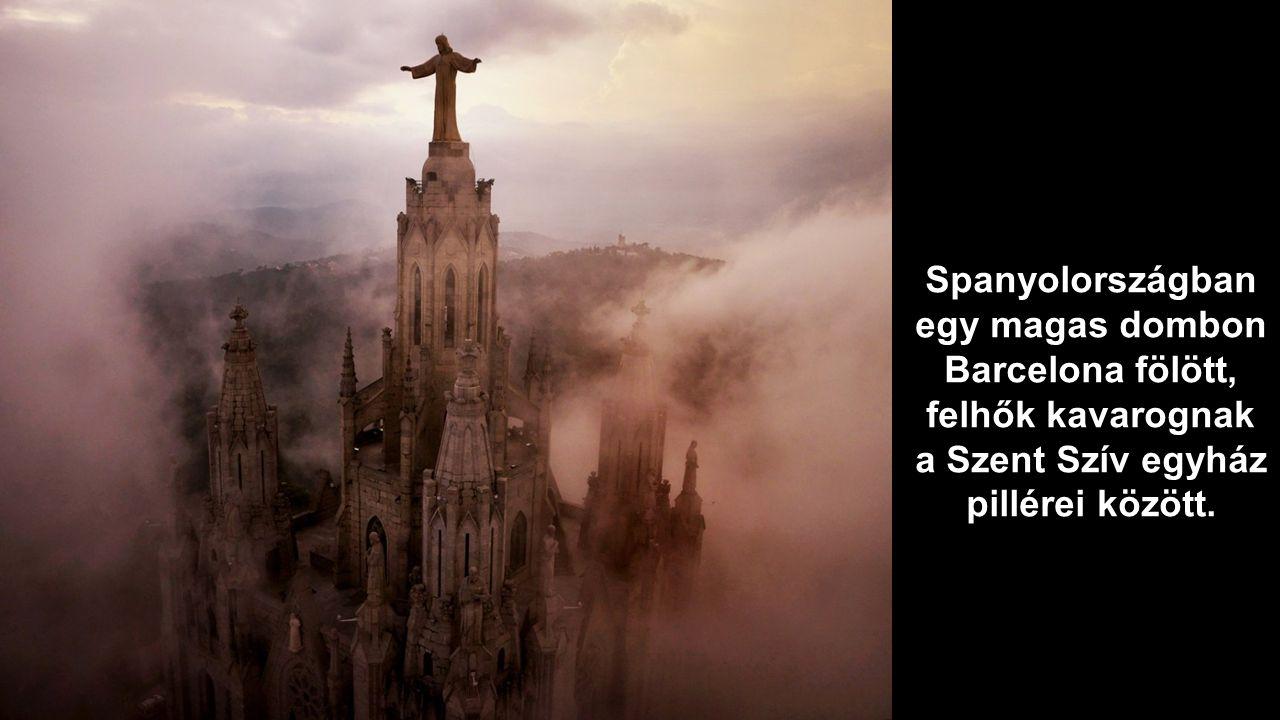 Spanyolországban egy magas dombon Barcelona fölött, felhők kavarognak a Szent Szív egyház pillérei között.